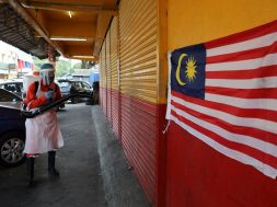 A worker sprays disinfectant at a shop, amid the coronavirus disease (COVID-19) outbreak in Kuala Lumpur