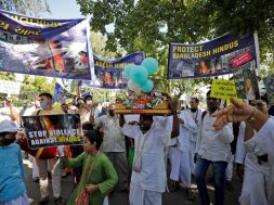 People hold banners and placards during a protest march organised by ISKCON to condemn attacks against Hindus during Durga Puja festival in Dhaka, in Ahmedabad